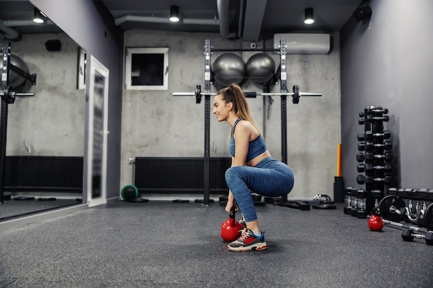 Sports exercises for life and endurance with kettle weights. side view of a sexy woman in sportswear and in good shape lifting weights in the gym. body stability, muscle flexibility and sports life