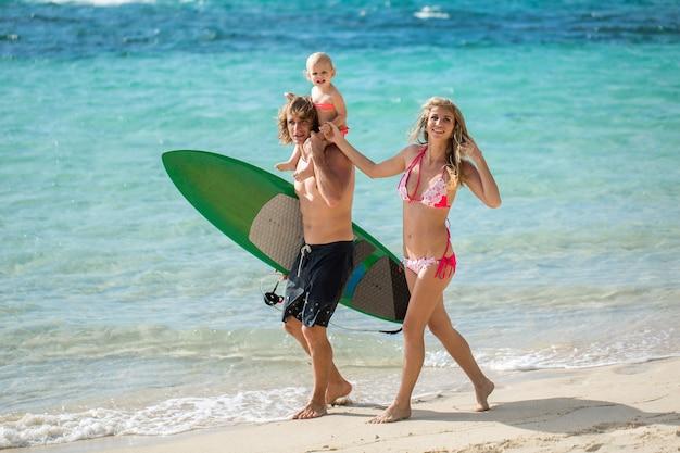 ビーチを歩くスポーツ家族のお父さん、お母さんと娘