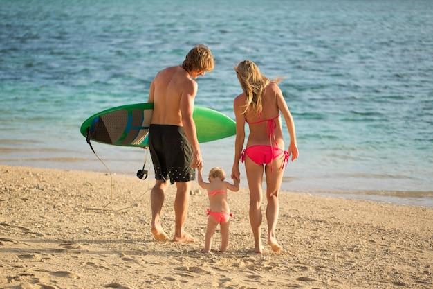 Спортивные семейные папа, мама и дочь гуляют по пляжу