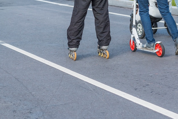 Спортивная семья. женские ножки в брюках и кроссовках на самокате. женщина верхом на самокате. ноги подростков, катающихся на роликовых коньках по улице. очень активные выходные.
