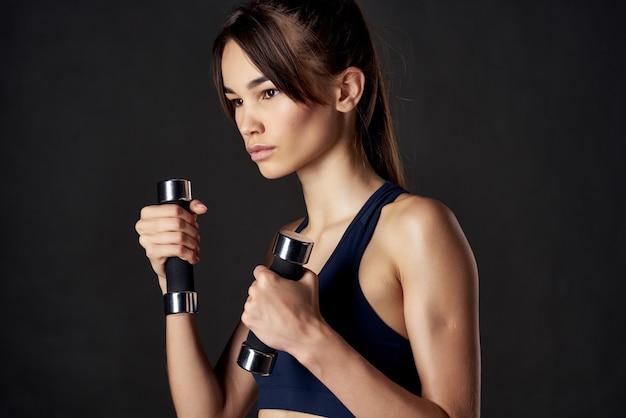 手にダンベルを持つ女性のスポーツフィギュアは、モチベーション暗い背景を行使します
