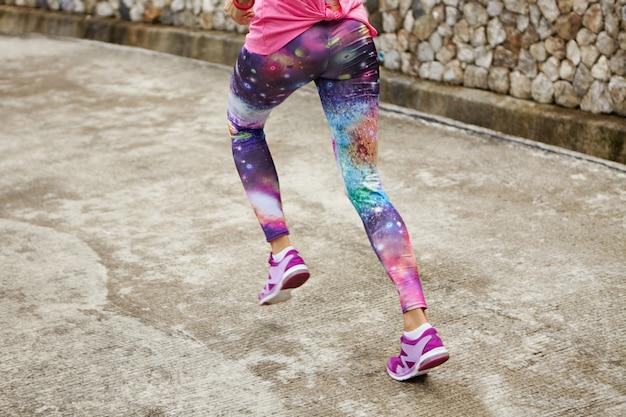 Спорт, фитнес и здоровый образ жизни. заморозьте действие выстрел подходящей женщины в стильных леггинсах с космическим принтом, бегущей по дороге.