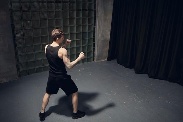 スポーツ、フィットネス、決意のコンセプト。黒のスニーカー、ショートパンツ、タンクトップで筋肉質の若い男性キックボクサーの背面図は、彼の前に拳を持って、空の部屋でパンチに取り組んでいます