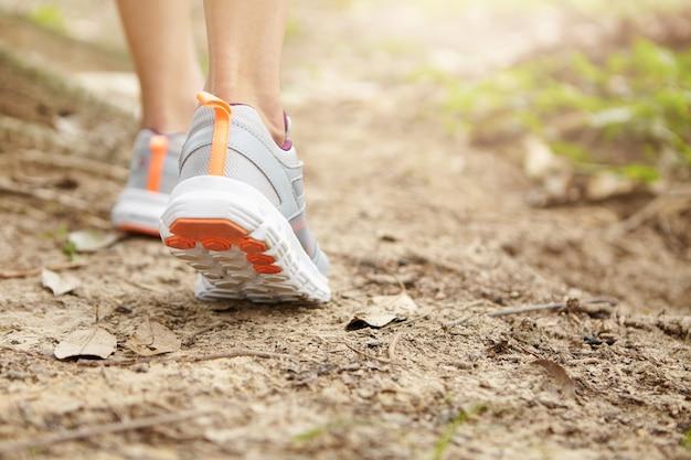 スポーツ、フィットネス、健康的なライフスタイルのコンセプト。フリーズアクションは、歩道でウォーキングやジョギングの女性ランナーのクローズアップ。公園でハイキングしながらランニングシューズを身に着けている若い運動女性。