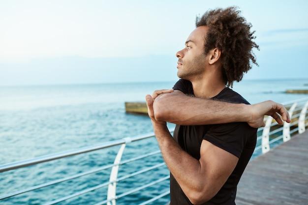 스포츠, 피트니스 및 건강한 라이프 스타일. 팔과 어깨 스트레칭 운동을하고 바다로 팔을 뻗으면서 집중된 아프리카 계 미국인 남자 주자를 맞추십시오.