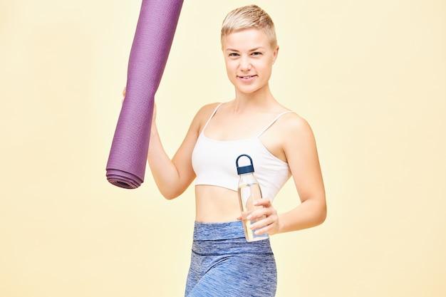 スポーツ、フィットネス、幸福の概念。スタイリッシュなトップとレギンスの魅力的なかわいい若い女性は、水のボトルと折りたたまれたヨガマットを保持し、練習後にエネルギーに満ちていると感じています