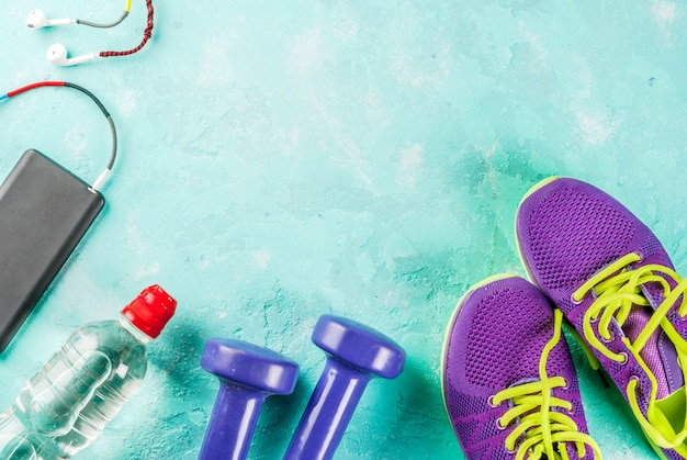 Sports, fitness concept. running sneakers, water bottle, headphones, dumbbells, phone, on a light blue background top view copy space