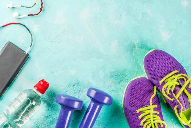 スポーツ、フィットネスの概念。実行中のスニーカー、水のボトル、ヘッドフォン、ダンベル、電話、明るい青の背景トップビューコピースペース