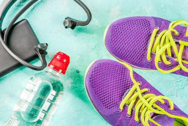 Sports, fitness concept. running sneakers, water bottle, headphones, dumbbells, smartphone, on a light blue  top view  copyspace