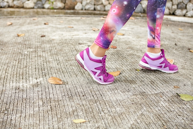 Sports, fitness and healthy lifestyle concept. close up shot of female feet in purple sneakers on pavement. sportswoman in space print leggings and stylish running shoes jogging on road in park