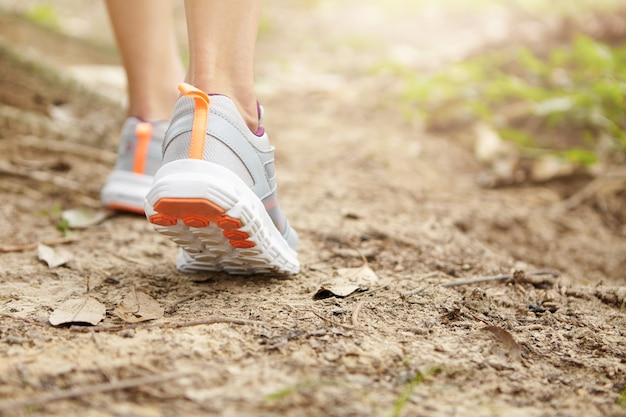 Sports, fitness and healthy lifestyle concept. freeze action close up of female runner walking or jogging on footpath. young athletic woman wearing running shoes while hiking in park.