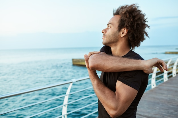Sports, fitness and healthy lifestyle. fit afro-american man runner looking concentrated while stretching his arms by the sea, doing arm and shoulder stretch exercise