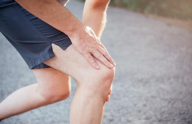 スポーツフィットネスの男性は、ランニングやジョギング時に膝の痛みに苦しんでいます