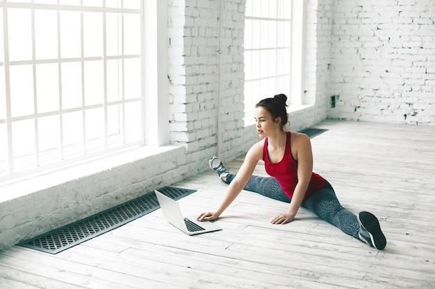 Sport, fitness e concetto di tecnologia moderna. donna che pratica le spaccature laterali sul pavimento e contemporaneamente controlla la posta elettronica sul pc aperto di fronte a lei