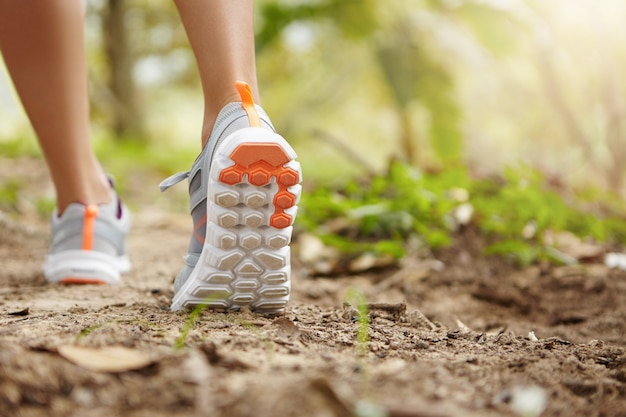 Sports, fitness, nature and healthy lifestyle concept. young female runner wearing sneakers or running shoes while hiking or jogging in park on sunny day.
