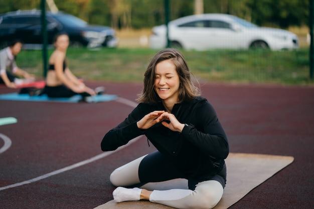 Sport e fitness fuori dalla palestra. giovane donna adatta in abiti sportivi si allena all'aperto nel parco giochi.