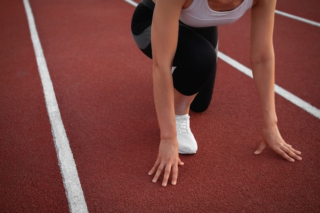 Sports and fitness. a young athletic woman in a white t-shirt and white sneakers getting ready to run at stadium track Premium Photo