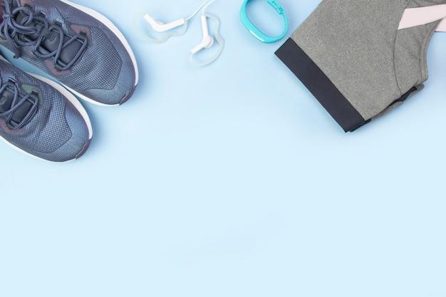 スポーツフラットレイアウト。青の背景にフィットネスアクセサリースニーカー、服、イヤホン、時計。自宅でスポーツやフィットネスをする。