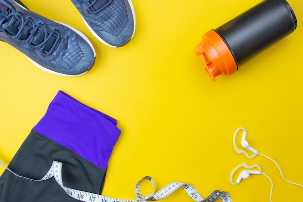 스포츠 평면 레이아웃. 피트니스 액세서리 운동화, 헤드폰, 옷, 파란색 배경에 병