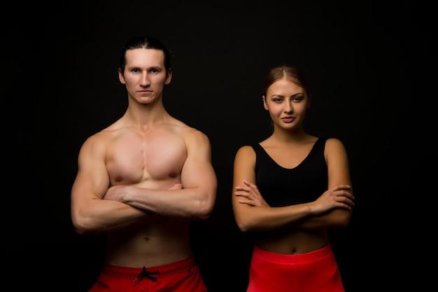 모두를 위한 스포츠. 섹시 맞는 커플 검은 배경. 프로 스포츠 팀. 운동 남자와 여자는 근육질의 팔을 교차 유지합니다. 운동을 통해 몸매를 유지합니다. 체육 및 스포츠.