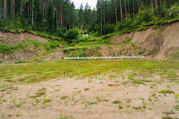 森の真ん中にあるトレーニング射撃場でのスポーツフロンティア。ターゲットとターゲットがあり、オープンなアルタイ、ベロクリハ、バイアスロンスポーツベースにあります。 Premium写真
