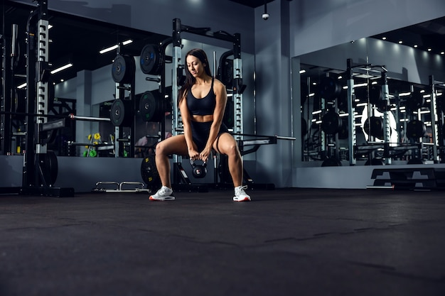 A sports girl in black sportswear is doing a cross-fit calorie-burning workout in an indoor gym with a dark atmosphere. she is in a squat position and holding a kettle bell in her hands. weight loss