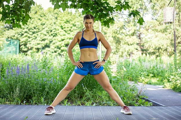 A sports girl in a blue tracksuit trains in the park stands in a pose with legs spread wide