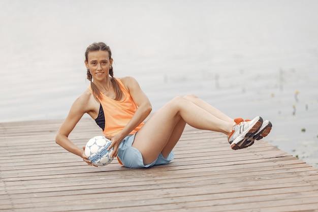 水でスポーツ少女。夏の公園の女性。オレンジ色のスポーツウェアの女性。