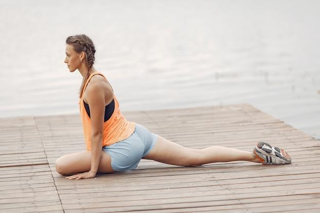 Спортивная девушка у воды. женщина в летнем парке. дама в оранжевой спортивной одежде.