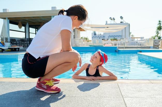 그녀의 어머니와 이야기하는 야외 수영장에서 수영복 모자 안경에 스포츠 여자 아이. 아이들의 활동적인 건강한 생활 방식.