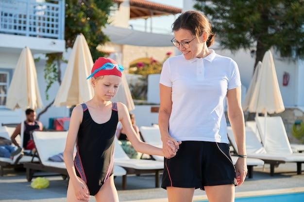 彼女の母親と一緒に屋外プールで水着キャップメガネのスポーツ女児。子供のアクティブで健康的なライフスタイル