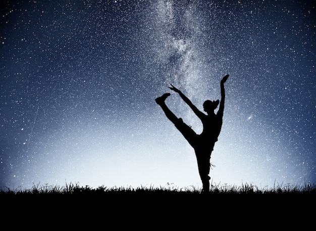 A sports girl at dawn is engaged in yoga. fitness classes at starry sky