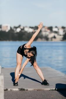 朝市のビーチの遊び場で実行する前に、黒の服を着てスポーツ少女がウォームアップ