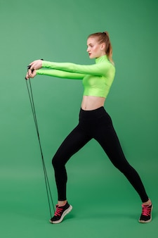 Sports girl in a green top with a rope on a green space. healthy lifestyle