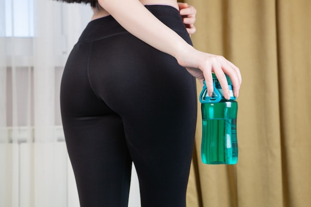 Спортивная девушка держит в руках бутылку воды