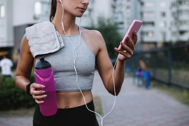 Спортивная девушка держит воду и телефон