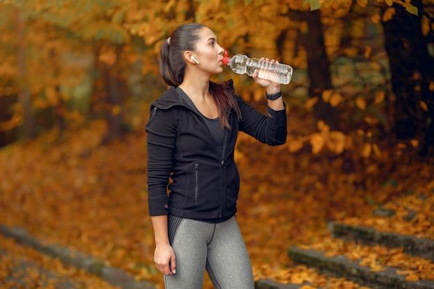 秋の公園で黒のトップトレーニングでスポーツ少女