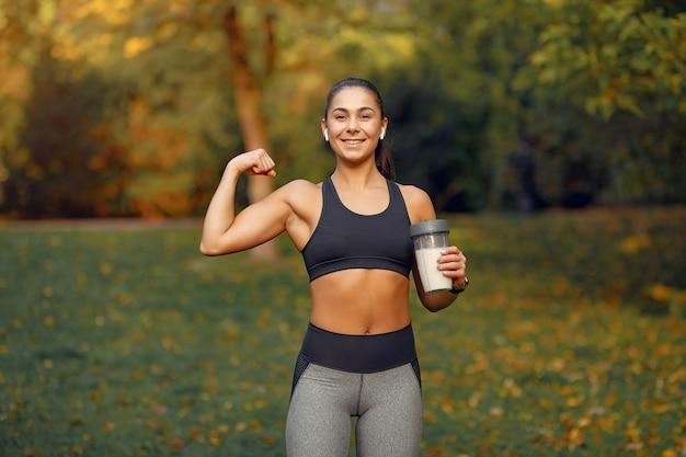 Спортивная девушка в чёрном топе тренируется в осеннем парке