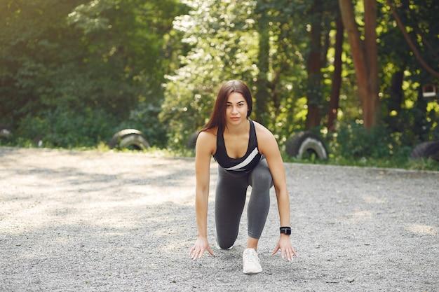 Спортивная девушка в чёрном топе тренируется в летнем парке