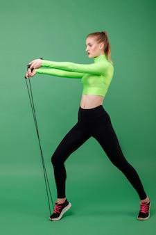 Спортивная девушка в зеленом топе с веревкой на зеленом пространстве. здоровый образ жизни