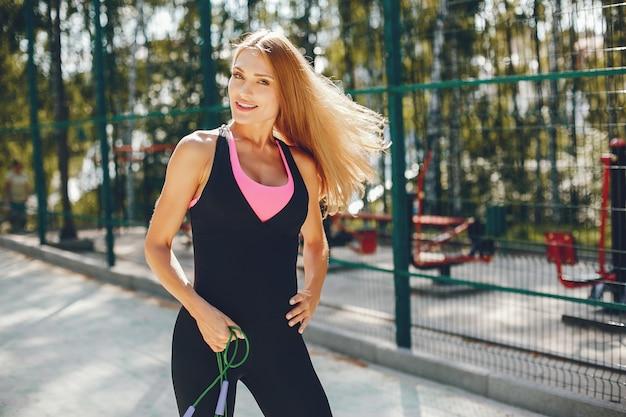 Спортивная девушка в утреннем летнем парке