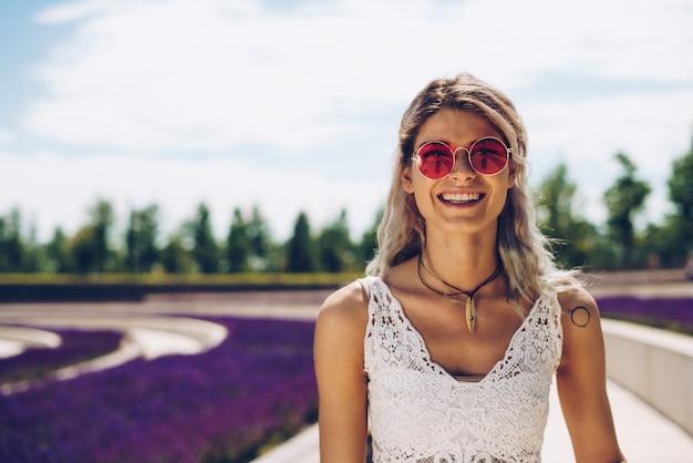 ピンクのメガネのスポーツの女の子は、咲くセージを背景に嬉しそうに笑う