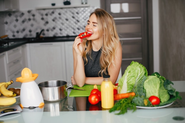 Sports girl in a kitchen with vegetables