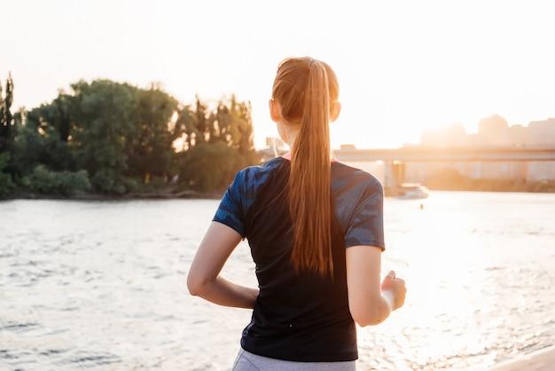 橋と公園を背景に、川の近くの街で走っているスポーツガール。背面図