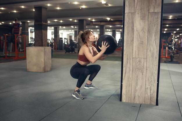 Спортивная девушка выполняет упражнение приседания и бросания медбола на фоне тренажерного зала