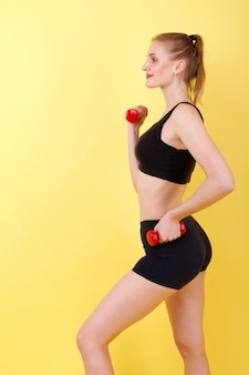 Sports girl performs weight training with dumbbells on a yellow space
