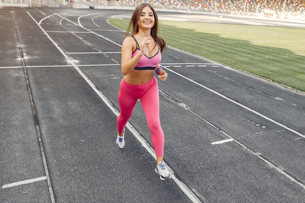Sports girl in a pink uniform runs at the stadium