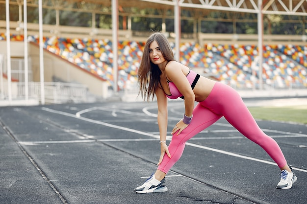 Sports girl in a pink uniform training at the stadium