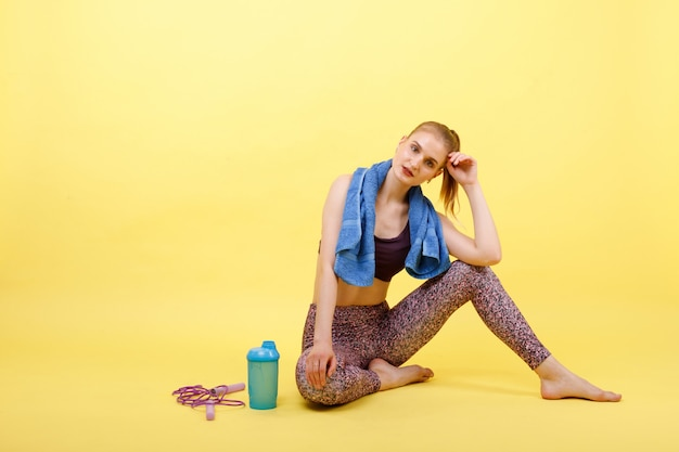 Sports girl rests after training. near the girl a bottle of water, a rope and a towel