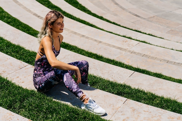 Sports girl sat down to relax on the steps of the park in a free pose